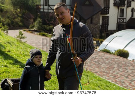 Father and son shoot arrows at a target.
