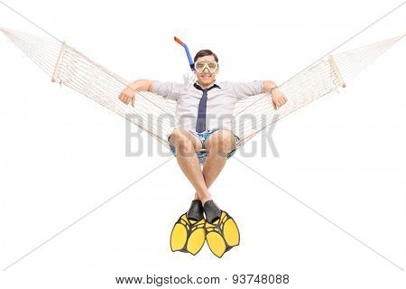 Studio shot of a young man with a snorkel and diving fins lying in a hammock and looking at the camera isolated on white background