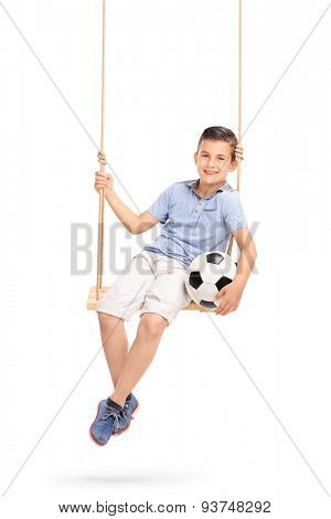 Vertical shot of a relaxed and joyful little boy holding a football seated on a wooden swing isolated on white background