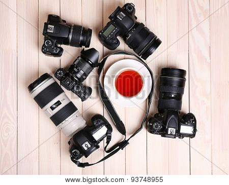 Modern cameras with cup of tea on wooden table, top view
