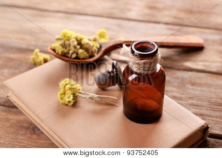 Old book with dry flowers and bottle on table close up