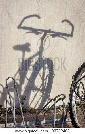 a wall shadow of mountain bicycle parked in racks - a commuting concept
