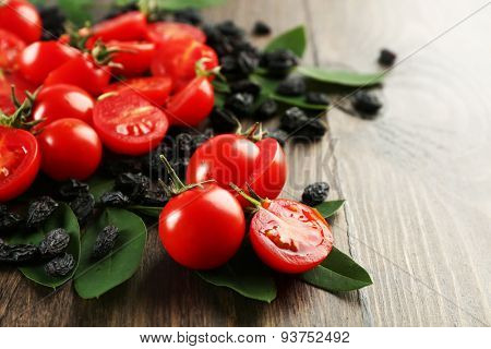 Cherry tomatoes with raisins on wooden background
