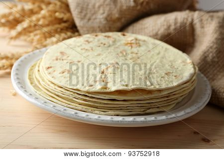 Stack of homemade whole wheat flour tortilla on plate, on wooden table background
