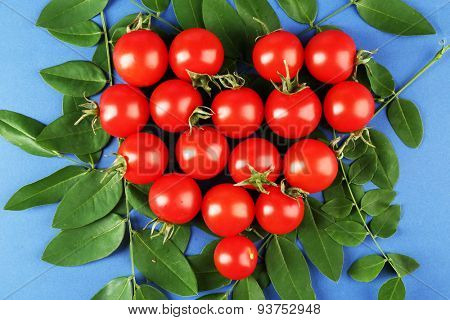 Cherry tomatoes arranged in heart shape with green leaves on blue background