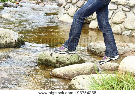 Hiking Boots And Legs Of A Woman Over A Mountain Stream