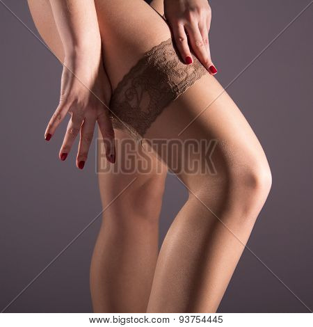 The Woman Wears A Nylon Stocking On Slender Leg
