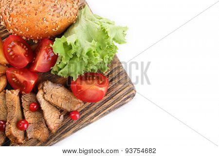 Beef with cranberry sauce, roasted potato slices and bun on wooden board, isolated on white