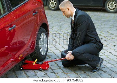 Man Using Red Hydraulic Floor Jack For Car Repairing