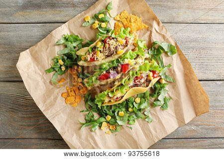 Tasty taco with greens on paper on table close up