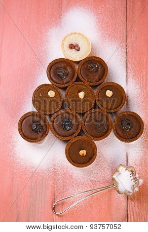 chocolate tartlets in christmas tree shape on pink wooden table