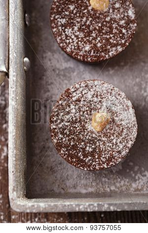 Chocolate  Mini Tartlets in vintage aluminium baking pan with dusting sugar