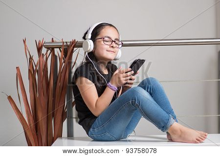 Cute girl with glasses listening to music