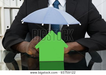 Businessman Protecting House Model With Umbrella
