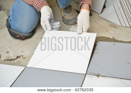 Worker installs ceramic tiles on a floor