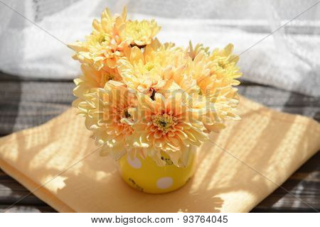 Beautiful chrysanthemums in pitcher on fabric background