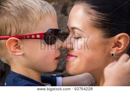Mom and son. Baby and mom near a stone wall, hugging, kissing, show love.
