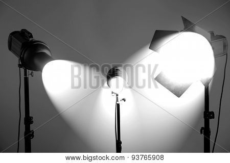 Photo studio with lighting equipment on grey wall background