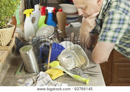 Man washing dirty dishes in the kitchen sink.