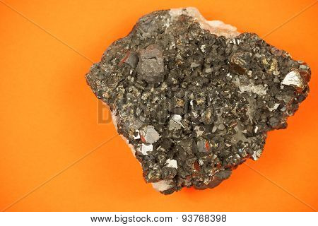 Piece of black lead ore with irregular texture, shot on orange paper background