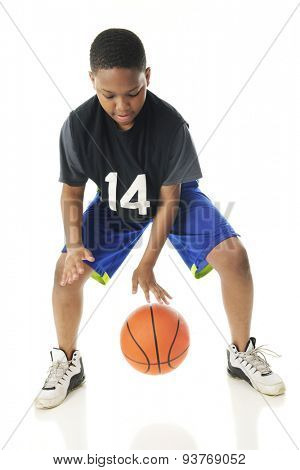 A preteen athlete rapidly dribbling his basketball close to the floor.  Motion blur on hands and ball.  On a white background.