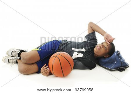 A preteen athlete on the floor, his gym bag as his pillow, after an exhausting basketball practice.  The basketball is at his side.  On a white background.