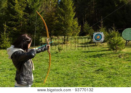 Young girl archer. Shooting with a bow.