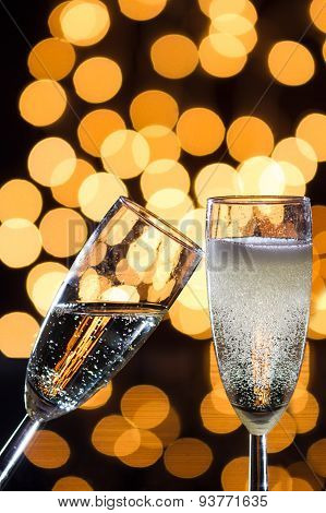 Two Champagne Glasses With Bubbles And Bokeh Lights In The Back
