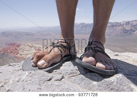 Rugged Feet In Primitive Sandals On Mountain