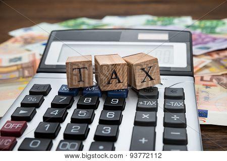 Tax Word On Wooden Blocks Over Calculator