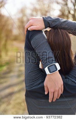 Smartwatch woman running with heart rate monitor. Closeup of female wrist wearing smart sport watch as activity tracker outdoors during cardio workout. Fitness girl stretching triceps during workout.