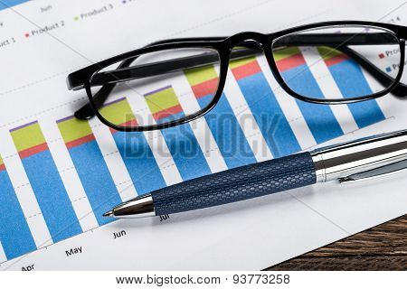 Financial Graph With Eyeglasses And Pen