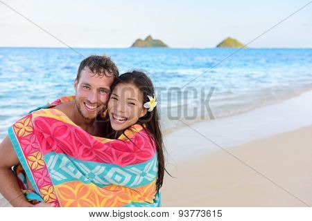 Swimming romantic couple wrapped in bathing towel on beach. Portrait of happy young interracial couple embracing each other having fun during holidays vacation travel. Asian woman, Caucasian man.