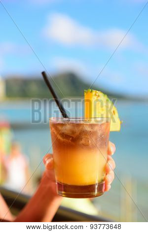 Mai Tai hawaiian drink on beach bar. Close up of alcoholic drink. Friends toasting having fun on Waikiki beach, Honolulu city, Oahu, Hawaii USA.