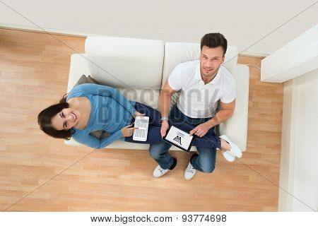 Smiling Young Couple Holding Digital Tablet