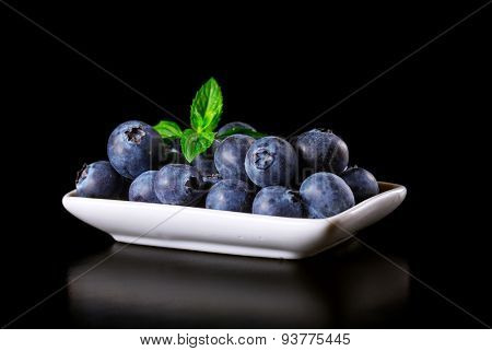 Fresh blueberries in a bowl on a black background