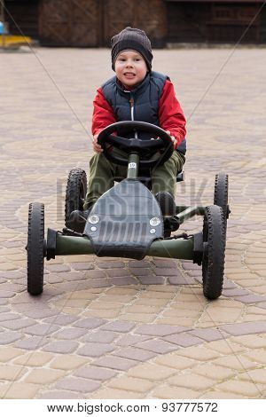 Boy riding a toy car