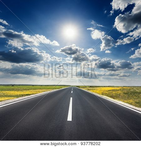 Driving On An Empty Asphalt Road Towards The Sun