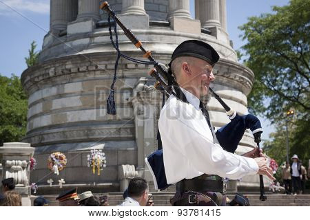NEW YORK - MAY 25 2015: Bagpiper from New York Scottish Pipes and Drums plays at the Memorial Day Observance service held at the Soldiers and Sailors Monument in Manhattan during Fleet Week NY 2015.