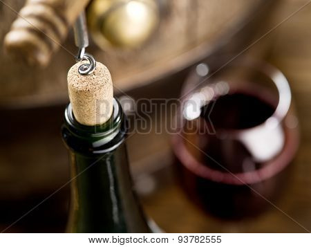 Opening of a wine bottle with corkscrew with wooden barrel on the background.