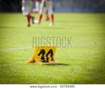 american football game yard markers with out of focus players in the background