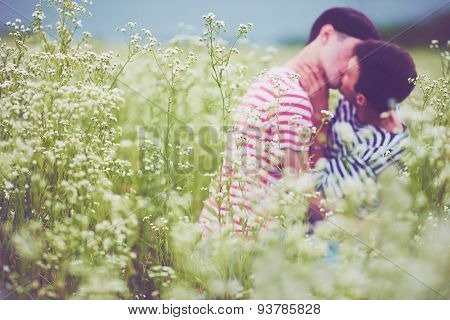Defocused Male Couple Kissing In Daisy Flowers, On Summer Field