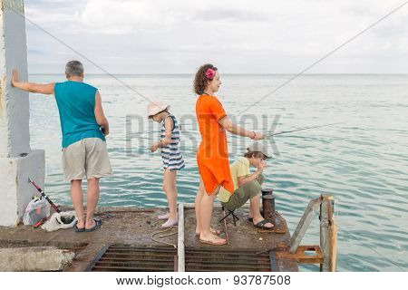 family of four go fishing on the docks
