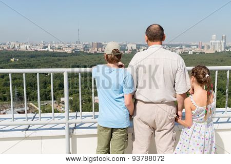 Grandfather with grandchildren admire the city view from the roof