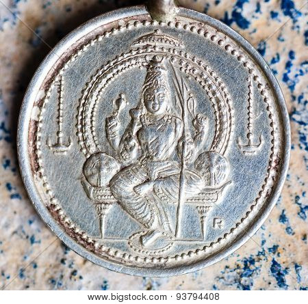A silver pendent or coin depicting Goddess Parvati