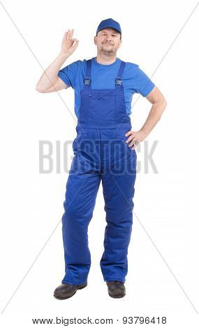 Man in blue overalls show ok sign.