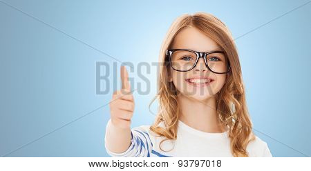 education, school, childhood, people and vision concept - smiling cute little girl with black eyeglasses showing thumbs up gesture over blue background