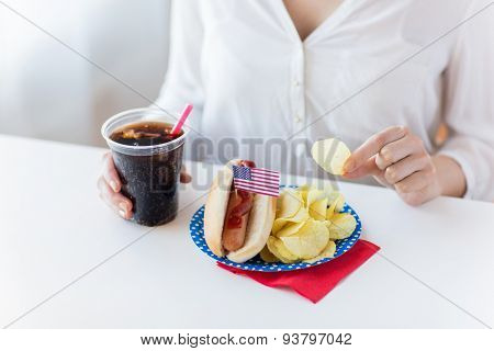 american independence day, celebration, patriotism and holidays concept - close up of woman eating potato chips with hot dog and coca cola in plastic cup on 4th july at home party