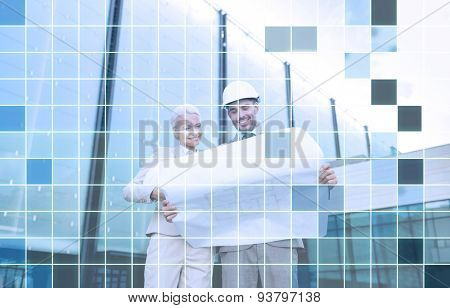 business, partnership, architecture and people concept - smiling businessman and businesswoman with blueprint and helmets over city street and blue grid background