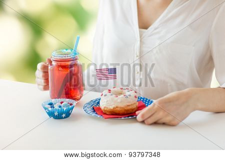 independence day, celebration, patriotism and holidays concept - close up of woman eating glazed donut, drinking juice from big glass mason jar and celebrating 4th july over green natural background